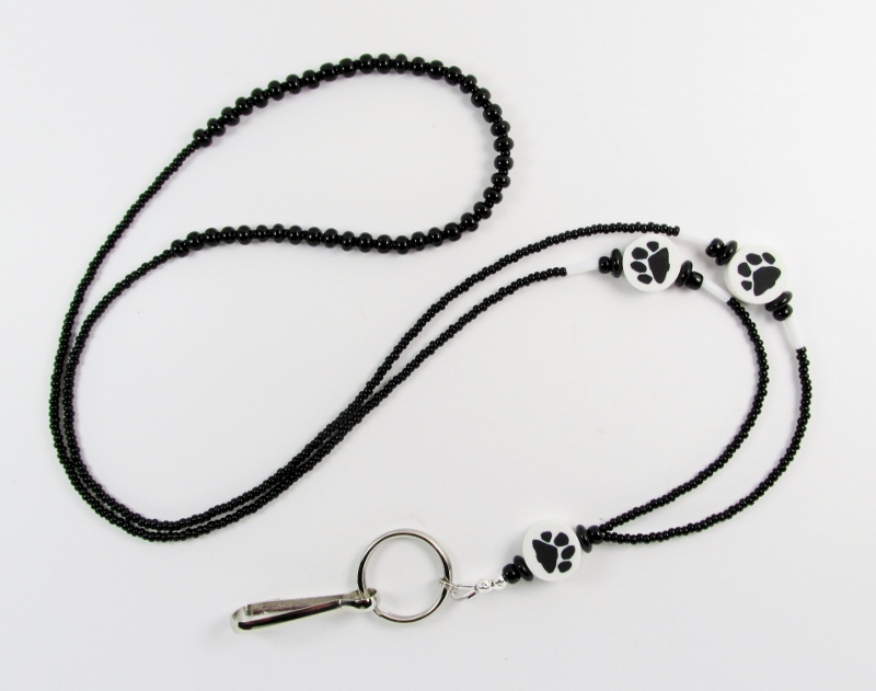Black and white glass beaded lanyard with black paw print beads